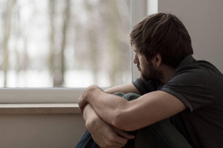 Młody mężczyzna  z jesienną chandrą patrzy przez okno. Żal, smutek i rozpacz.